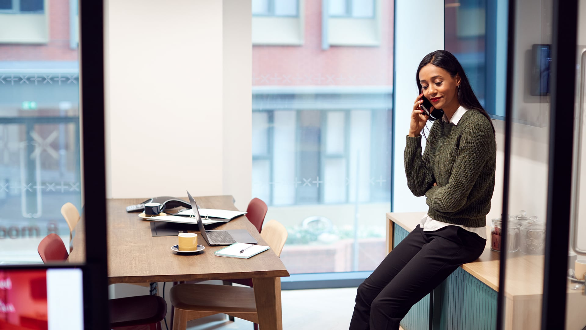 A property manager in her office talking to a contractor on the phone