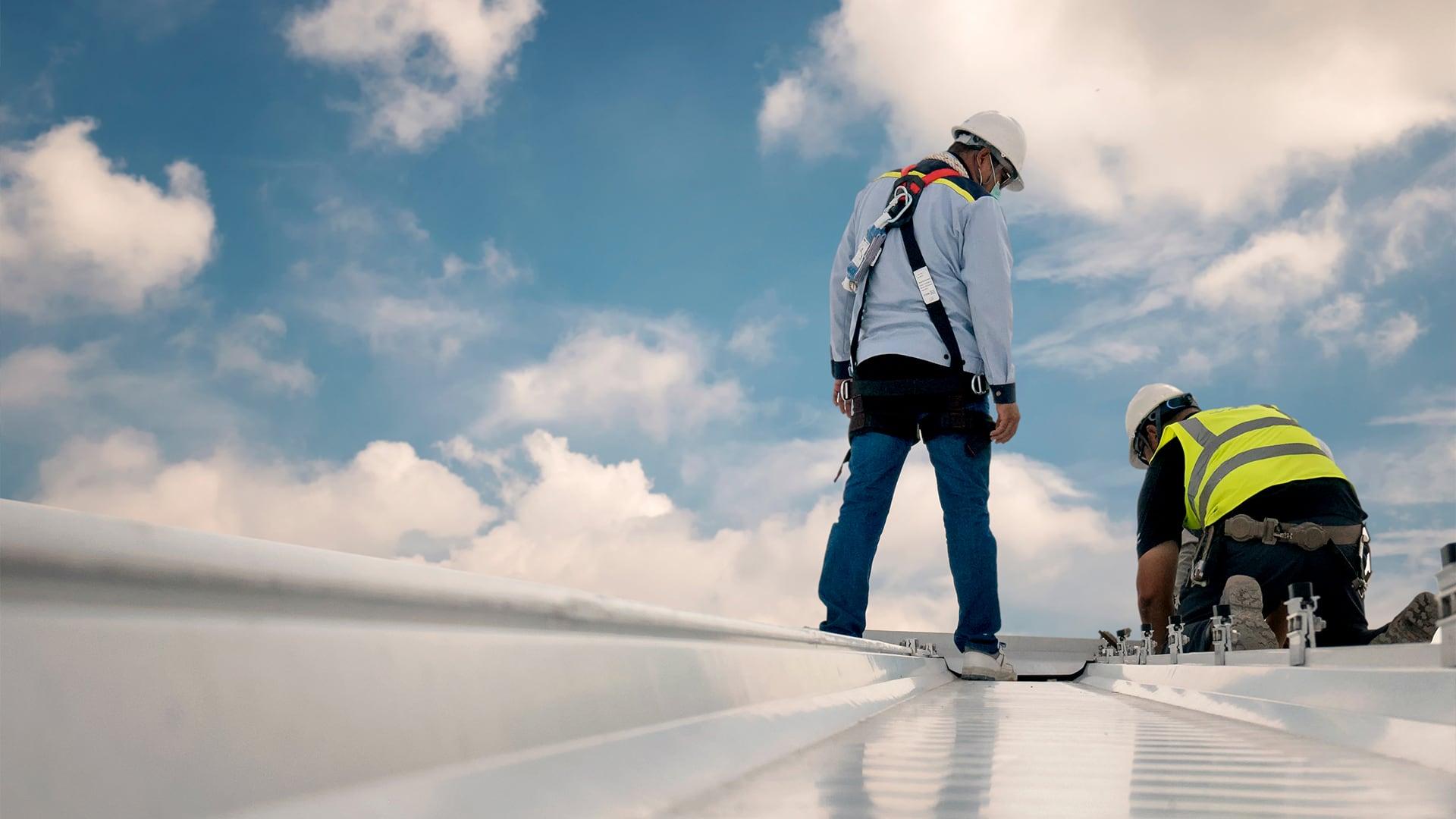 Roofing contractors repairing a metal roof